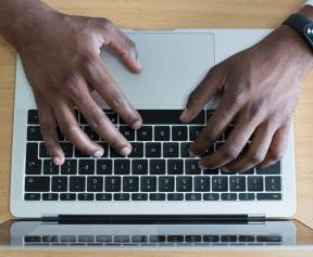Pros of Blogging - Hands typing on a laptop