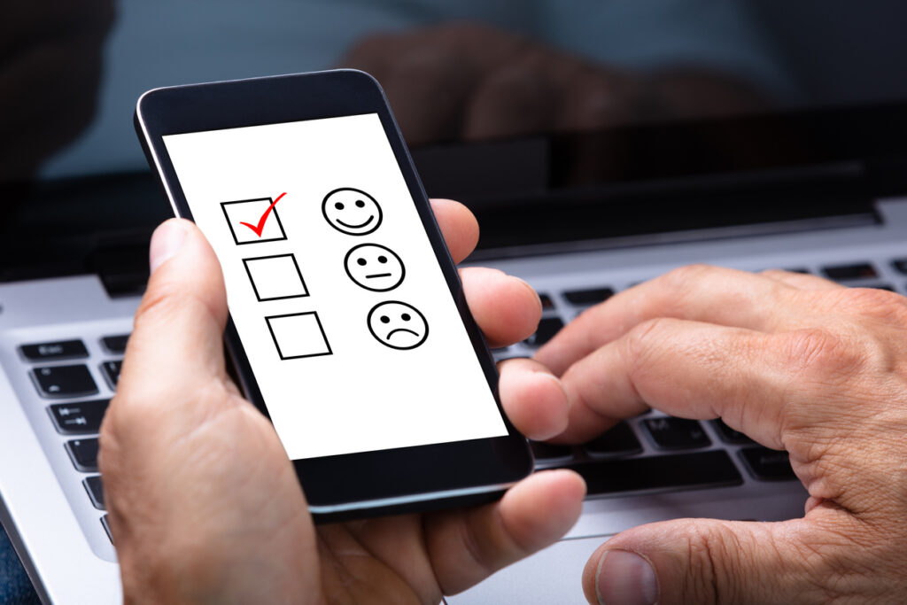 CAN-SPAM Compliance Checklist: Close-up Of A Man's Hand Holding Smartphone With Ticked Checkbox And Smile Icon On Screen