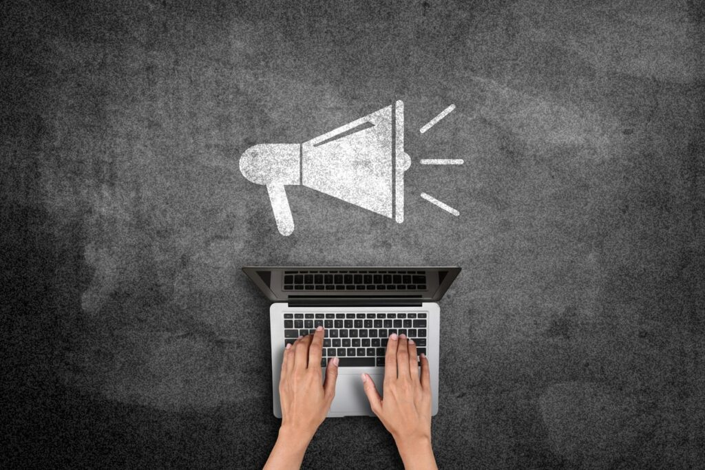 Online Marketing Strategies for Recruitment - Job Boards: Aerial view of hands typing on laptop with megaphone icon above