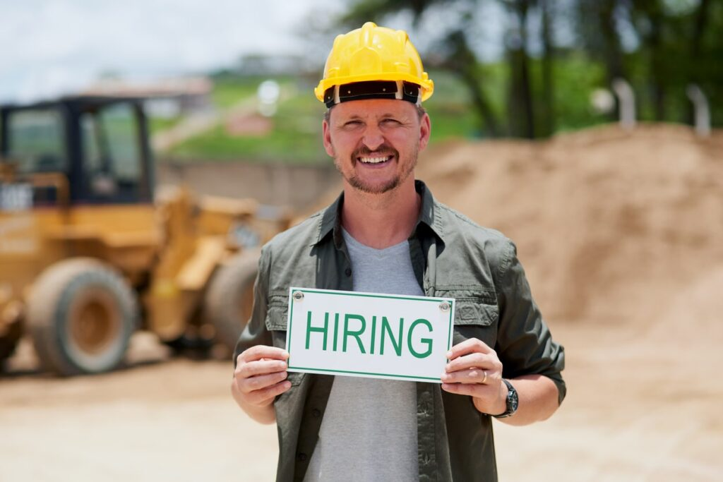 "Online Marketing Strategies for Recruitment - Man in construction hat in front of equipment holding sign that says ""Hiring"""