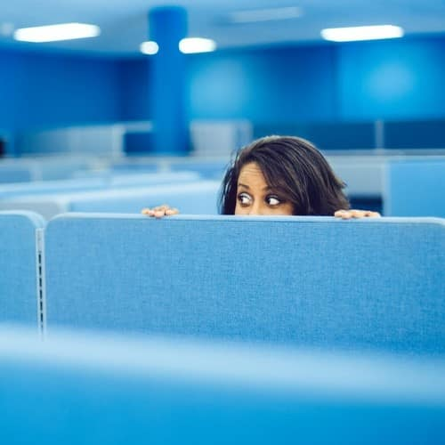 Not Setting Goals - Dark-haired woman peeking over cubicle wall